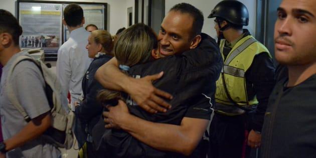 Eduardo Salazar, membre de la police du district de Chacao, enlace une collègue alors qu'il revient sur son lieu de travail après avoir été libéré de prison dans une vague de libérations de Noël par le président Nicolas Maduro.