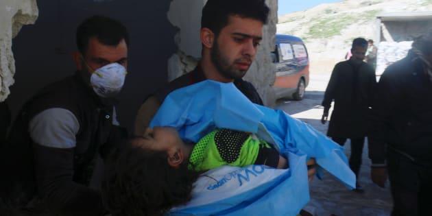 I soccorritori portano via il corpo di un bambino morto a Khan Sheikhoun, in Siria