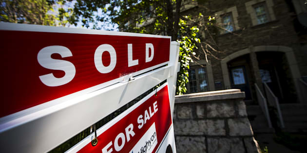 "A ""For Sale"" sign stands in front of a home that has been sold in Toronto,  June 29, 2015."