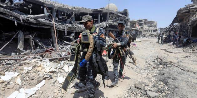 Miembros de la Policía Federal de Irak trasladan cinturones preparados por el ISIS para cometer atentados suicidas, tras la toma de la ciudad vieja de Mosul.