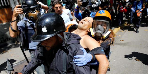 Un hombre herido en una manifestación contra el Gobierno en Caracas es llevado a una moto para ser tratado en un hospital, este miércoles.