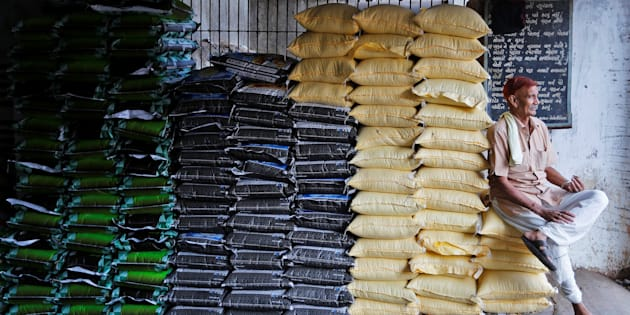 A labourer sits on sacks of food grains while waiting for customers at a wholesale market in Ahmedabad.