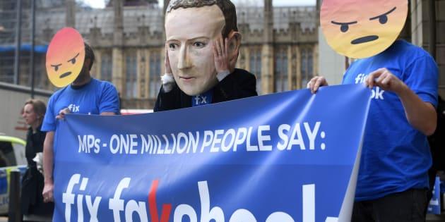 Des usagers de Facebook manifestent devant le parlement britannique.
