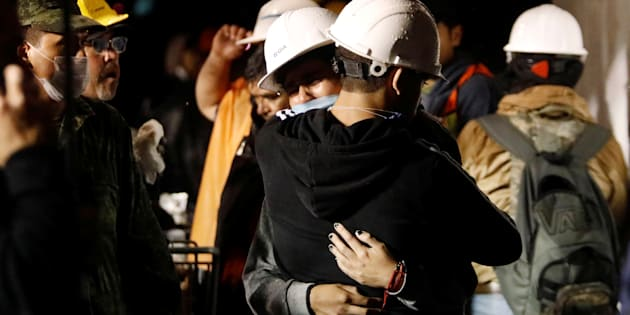 Workers hug during the search for students at Enrique Rebsamen school.
