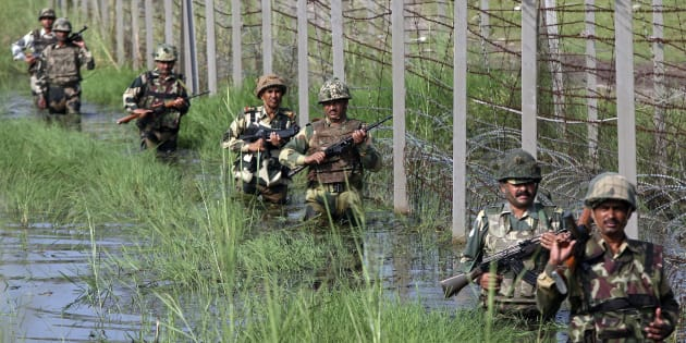 Indian Border Security Force (BSF) soldiers patrol the fenced border with Pakistan.