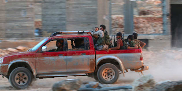 Fighters of the Syrian Islamist rebel group Jabhat Fateh al-Sham, the former al Qaeda-affiliated Nusra Front, ride on a pick-up truck in the 1070 Apartment Project area in southwestern Aleppo, Syria August 5, 2016. REUTERS/Ammar Abdullah