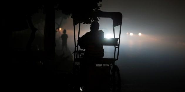 A rickshaw puller waits for customers along a roadside amidst heavy smog in New Delhi, India November 6, 2016.