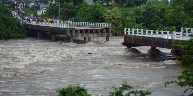 Este folleto impreso por la Agencia Cubana de Noticias muestra a los residentes de la ciudad de Zaza del Medio mirando un puente derrumbado, causado por las fuertes lluvias asociadas con la tormenta tropical Alberto.