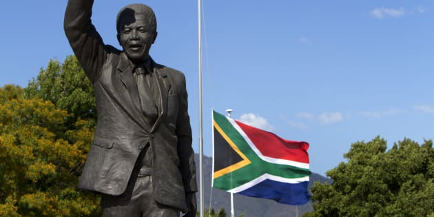 The South African flag flies at half mast behind the iconic Mandela statue at the entrance of the Groot Drakenstein Prison (formerly Victor Verster Prison) situated in the Cape Winelands outside Cape Town. December 9, 2013.