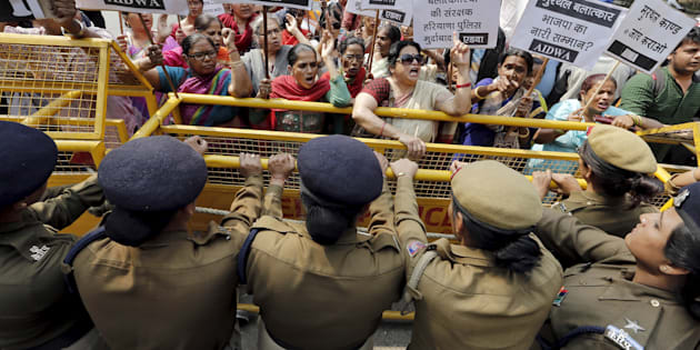 Activists from All India Democratic Women's Association (AIDWA) shout slogans behind a police barricade outside the Haryana Bhawan during a protest in New Delhi, India, February 29, 2016.