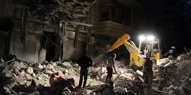 Civil Defense members search for survivors at a site hit by an airstrike in the rebel-held al-Shaar neighbourhood of Aleppo, Syria, September 27, 2016.
