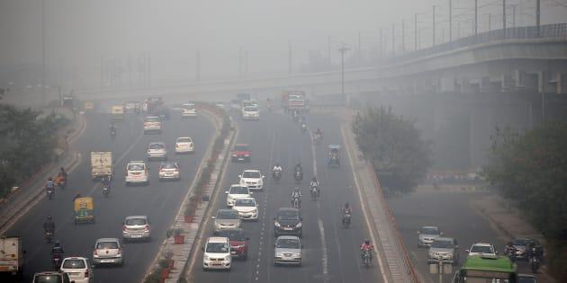 Traffic drives through smog in Delhi.