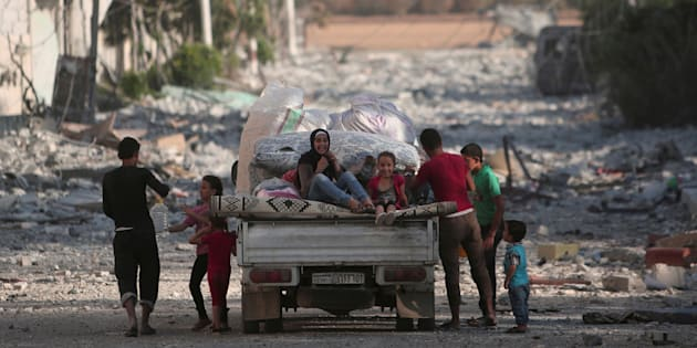 Children sit on a pick-up truck loaded with belongings along a damaged street in Manbij, Aleppo Governorate, Syria, August 16, 2016. REUTERS/Rodi Said