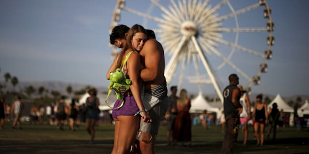 A couple hugs in front of the ferris wheel at the Coachella Valley Music and Arts Festival in Indio, California April 10, 2015. REUTERS/Lucy Nicholson      TPX IMAGES OF THE DAY