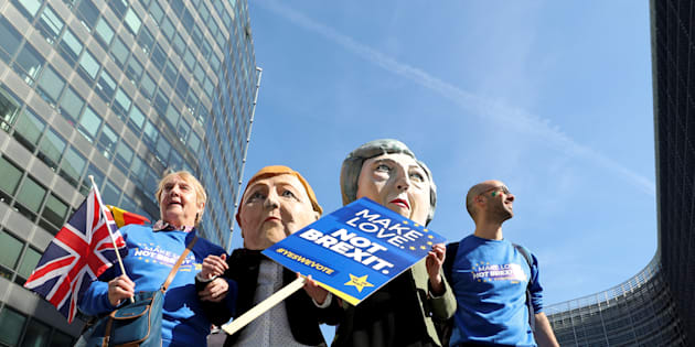 Protesters dressed as German Chancellor Angela Merkel and Britain's Prime Minister Theresa May pose with anti-Brexit demonstrators ahead of a EU Summit in front of European Commission headquarters in Brussels, Belgium March 21, 2019.  REUTERS/Yves Herman