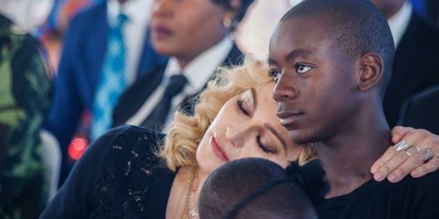 Madonna rests her head on the shoulder of her son David Banda during the opening ceremony of the Mercy James Children's Hospital at Queen Elizabeth Central Hospital in Blantyre, Malawi, on July 11, 2017. (AMOS GUMULIRA/AFP/Getty Images)