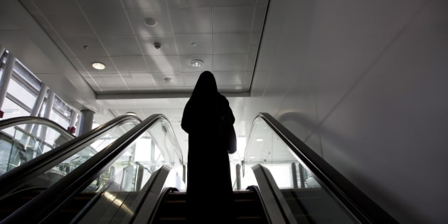 United Arab Emirates, Dubai, Arab Woman in a Hijab Walking Escalator