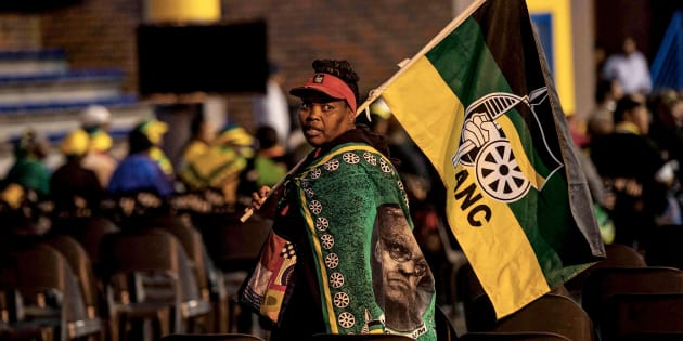 ANC supporter walks with the party's flag at the Orlando Communal Hall on November 13, 2017 in Johannesburg, South Africa.