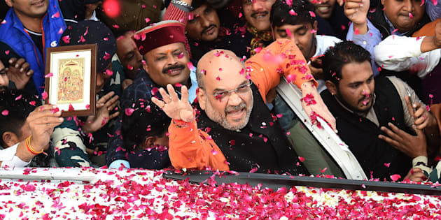 Indian Bharatiya Janata Party (BJP) President Amit Shah (C) shows the victory sign to supporters as he arrives to address a press conference at the party headquarters in New Delhi on December 18, 2017.