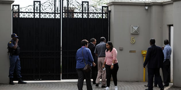 Members of the South African Asset Forfeiture Unit and other law enforcement agencies arrive to search the Gupta family compound on April 16, 2018 in Johannesburg.