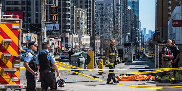 A body lies covered on the sidewalk in Toronto after a van mounted a sidewalk, crashing into a number of pedestrians on April 23, 2018.