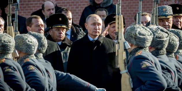 """Le Premier ministre Dmitri Medvedev (à gauche), le Président russe Vladimir Poutine et le ministre de la défense Sergueï Choïgou (à droite) assistent à la cérémonie du """"Défenseur de la patrie"""" à Moscou, le 23 février 2018."""