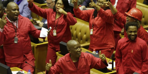 EFF leader Julias Malema (C, bottom) celebrates prior to an unsuccessful vote of no-confidence against President Jacob Zuma on August 8, 2017 in the South African National Assembly in Cape Town.