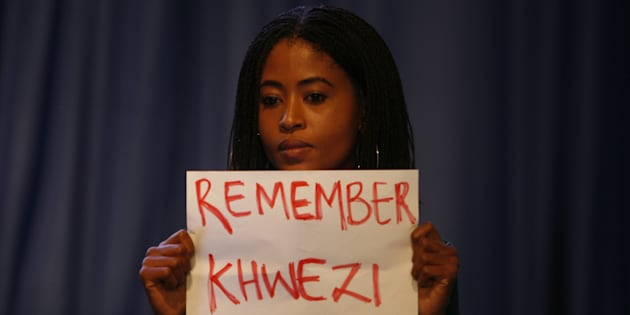 A young woman holds a poster written Remember Khwezi during President Jacob Zumas speech at the IEC briefing after the 2016 local government elections on August 06, 2016 in Pretoria, South Africa. Four women staged an anti-rape silent protest directed at Zuma while he delivered his speech during the announcement of the final election results.