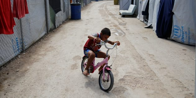A boy rides a bicycle at the Souda municipality-run camp for refugees and migrants, on the island of Chios, Greece, September 7, 2016. REUTERS/Alkis Konstantinidis