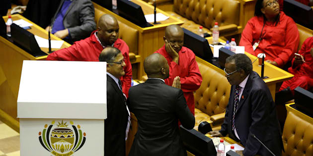 Opposition party leaders Mmusi Maimane (DA party), Julius Malema (EFF party) and Mangosuthu Buthelezi (IFP party)  confer shortly before voting during the motion of no confidence against South African president Jacob Zuma in parliament last year.