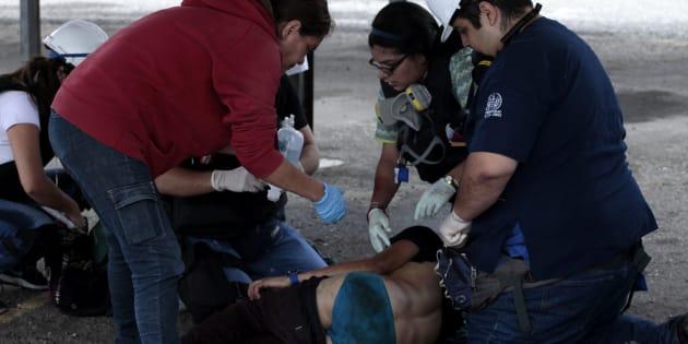 Sanitarios asisten a una persona herida durante un enfrentamiento entre manifestantes opositores y la Guardia Nacional Bolivariana en Barquisimeto (Venezuela).