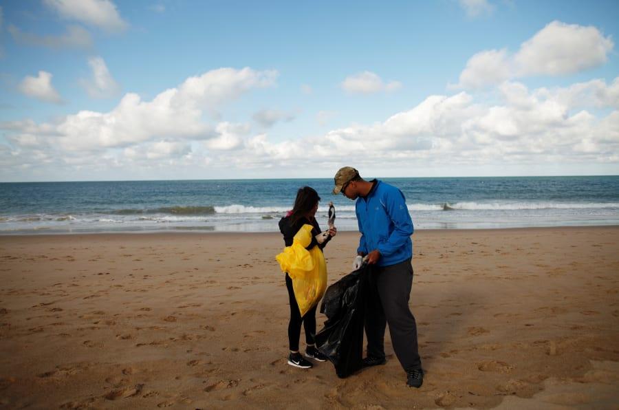 Imagen de voluntarios recogiendo basura y plástico en una playa de España.