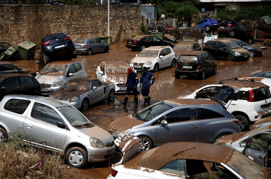 Miembros del equipo de rescate camina entre los automóviles daños luego de las inundaciones en el suburbio de Maroussi, cerca de Atenas.