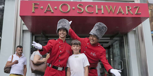 A boy has his photo taken outside the FAO Schwarz toy store in New York City, July 15, 2015.  A pop-up version of the iconic U.S. toy store is coming to The Bay stores in Canada this holiday season.