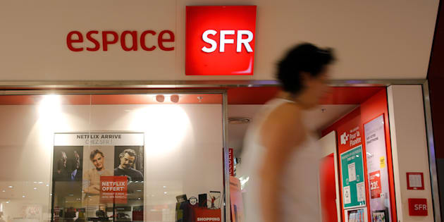 A woman walks past a shop of French telecoms operator SFR in Saint-Sebatien-sur-Loire near Nantes, France, July 20, 2017. REUTERS/Stephane Mahe