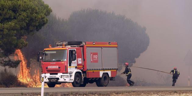 Un grupo de bomberos intenta apagar un foco de fuego en la carretera entre Mazagón y Matalascañas, el pasado día 25.