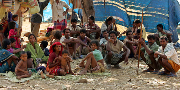 A group of Indian tribe sit in open at a camp in Dornapal in Chhattisgarh, India March 8, 2006. More than 45,000 people have left their homes to live in camps run by the Salwa Judum, but have just bows and arrows to defend themselves against the rebels' guns and explosives. Picture taken March 8, 2006.  REUTERS/Kamal Kishore
