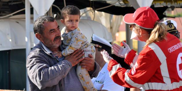 Una miembro de Cruz Roja atiende a un adulto y a un niño a su llegada al puerto de Palermo a bordo del 'Aquarius', el 13 de octubre pasado.