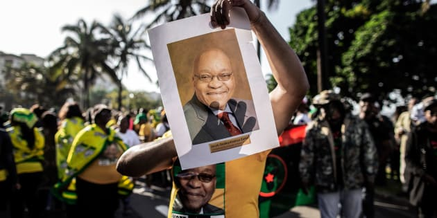 A supporter wearing the colours of the ANC and holding a portrait of former South African president Jacob Zuma takes part in a rally in support of  Zuma on June 8, 2018 outside the High Court, in Durban.