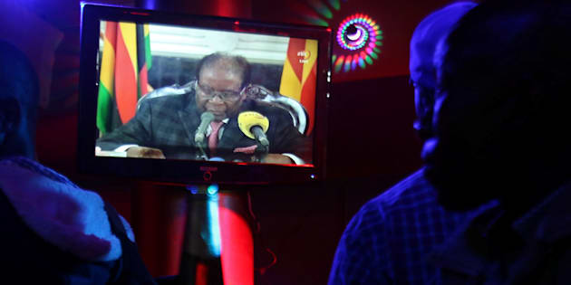People watch as Zimbabwean President Robert Mugabe addresses the nation on television, at a bar in Harare.