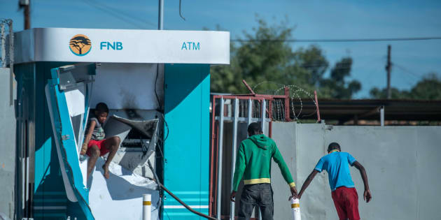 Children play around a vandalised ATM in North West on April 20, 2018, as protests continued for a second day in provincial capital Mahikeng. Police fired rubber bullets at protesters after President Cyril Ramaphosa cut short a foreign trip to deal with violent riots over alleged government corruption and poor public services. Shops were looted, roads were blocked and vehicles set alight. At least 23 people were arrested, and one man was reported to have died.