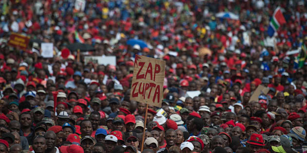 A protester holds a placard reading 'Zap Zupta', refering to Zuma and the Gupta Family.