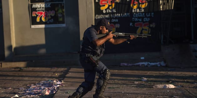 A South African riot police officer fires rubber bullets to prevent looting in North West on April 20, 2018, as protests continued for a second day in provincial capital of Mahikeng.