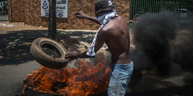 A demonstrator lights a tyre during protests outside Hoërskool Overvaal on January 17.
