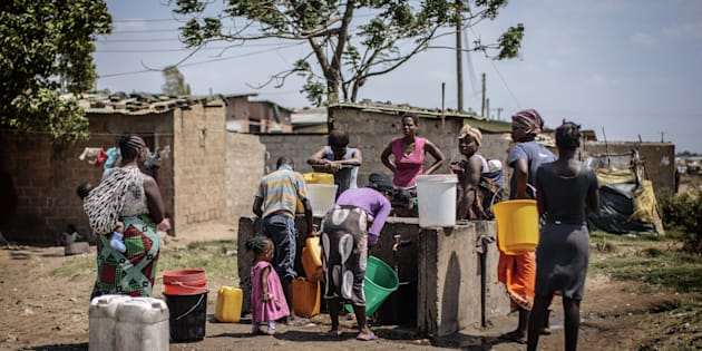People collect water at a water point in the 'compound' township on the oustkirts of Lusaka on November 12, 2014, a day after the burial of the late Zambian president.