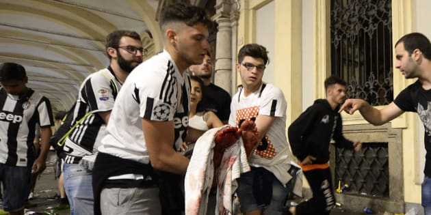 Juventus' supporters carry an injured woman in Piazza San Carlo after a panic movement in the fanzone where thousands of Juventus fans were watching the UEFA Champions League Final football match between Juventus and Real Madrid on a giant screen, on June 3, 2017in Turin. / AFP PHOTO / MASSIMO PINCA        (Photo credit should read MASSIMO PINCA/AFP/Getty Images)
