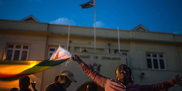 Harare residents celebrate in front of the parliament  after the resignation of Zimbabwe's president Robert Mugabe on November 21, 2017. The bombshell announcement sparks scenes of wild celebration in the streets of Harare, with car horns honking and crowds dancing and cheering over the departure of the autocrat who has ruled Zimbabwe since independence. / AFP PHOTO / MUJAHID SAFODIEN