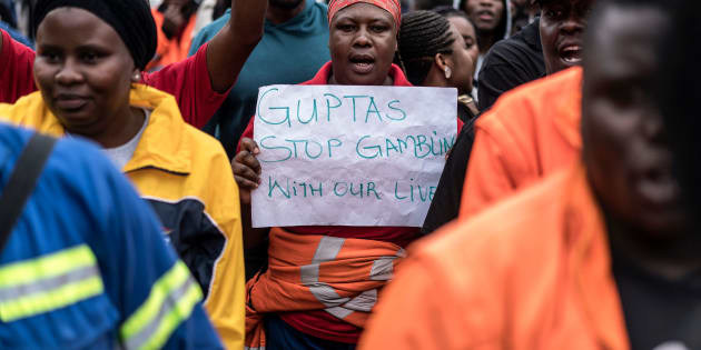 Employees and contractors of the Optimum Coal Mine in Hendrina, owned by the controversial Gupta family, demonstrate with a placard reading 'Guptas - stop gambling with our lives' in front of the gates of the mine in Hendrina, South Africa, on February 22, 2018.