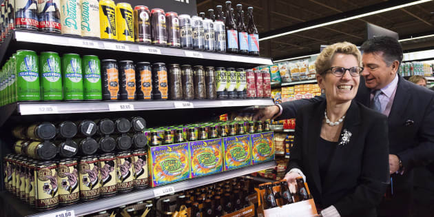 Ontario Premier Kathleen Wynne, left, and Minister of Finance Charles Sousa, right, pick beer at a Loblaws grocery store in Toronto on Dec. 15, 2015.