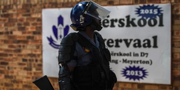 A South African riot police officer stands guard at the main entrance of Hoërskool Overvaal on January 18, 2017 in Vereeniging.